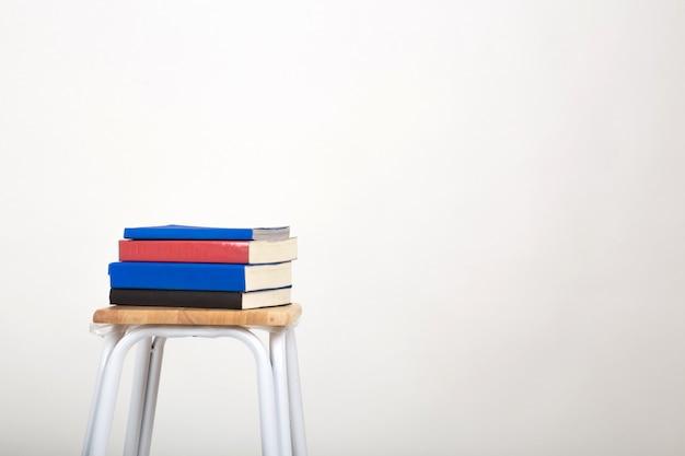 Una pila di libri su una sedia. isolato uno sfondo bianco.