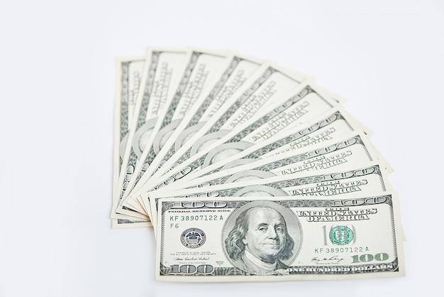 Una pila di mille dollari in cento banconote del dollaro isolate su una priorità bassa bianca.