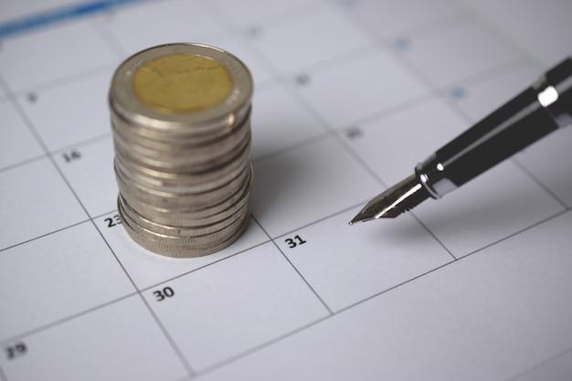 Una pila di monete e una penna sul calendario.