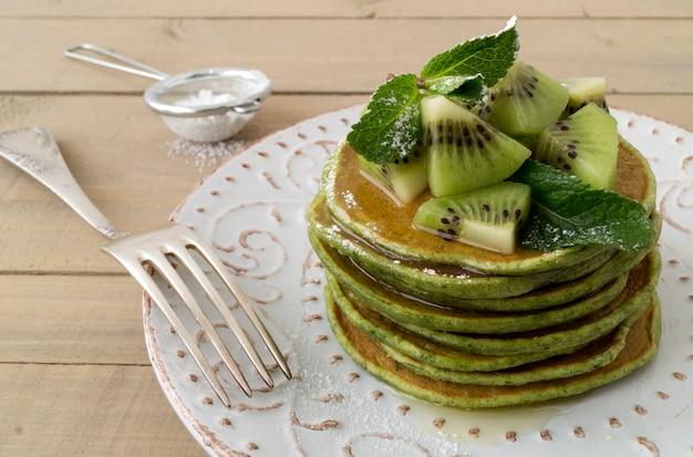 Una pila di pancake con sciroppo e kiwi.