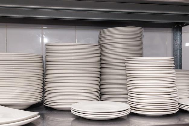 Una pila di piatti in ceramica bianca pulita su una griglia di metallo sul retro del ristorante