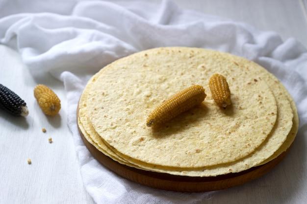 Una pila di tortillas di mais rotonde su tavola di legno e pannocchie.