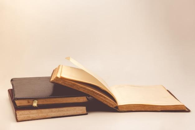 Una pila di vecchi libri con sfondo d'epoca.
