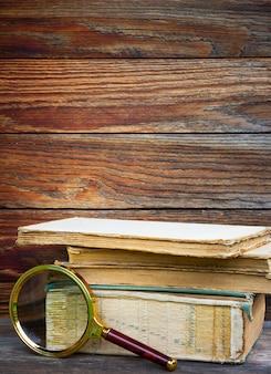 Una pila di vecchi libri e lente d'ingrandimento