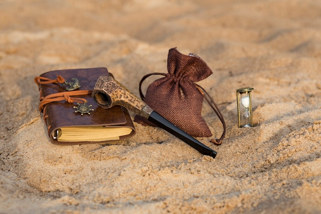 Una pipa da fumo, un sacchetto di tabacco, una clessidra e un libro per le voci