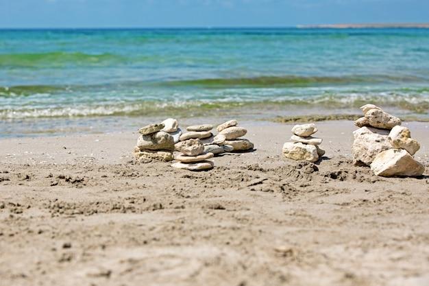 Una piramide di pietre su una spiaggia di ciottoli contro il mare e il cielo.