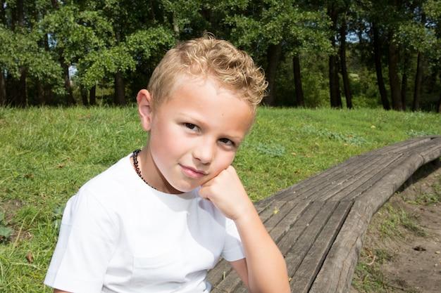 Una posa bionda allegra del bambino del ragazzo da dieci anni all'aperto