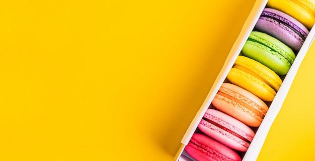 Una prelibatezza dolce francese, primo piano di varietà dei maccheroni. maccheroni francesi variopinti in scatola sulla vista moderna del piano d'appoggio con copyspace