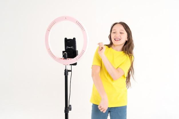Una ragazza adolescente balla e gira un video. selfie. il telefono è montato su un treppiede e la lampada ad anello brilla. emozione di gioia e gioia sul viso di un bambino.