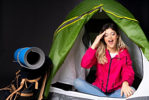 Una ragazza adolescente dentro una tenda da campeggio verde sul muro nero ha appena realizzato qualcosa e ha intenzione di risolverlo