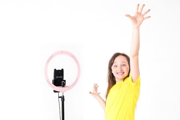 Una ragazza adolescente guarda la telecamera e alza la mano con un'espressione di gioia sul viso.