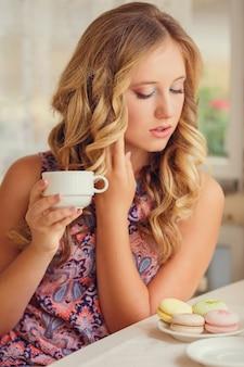 Una ragazza adorabile con capelli biondi che mangia dessert e che beve tè in un caffè