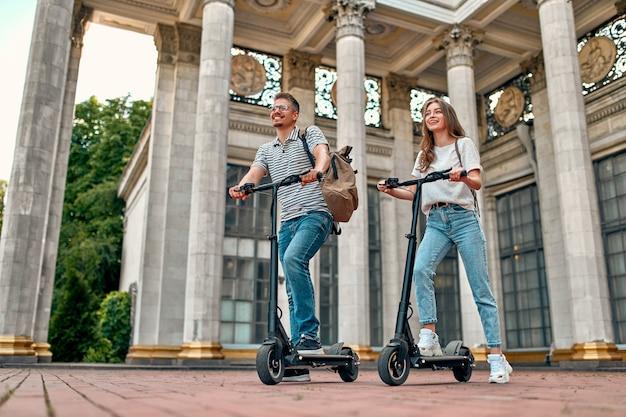 Una ragazza affascinante e un ragazzo attraente su scooter elettrici.