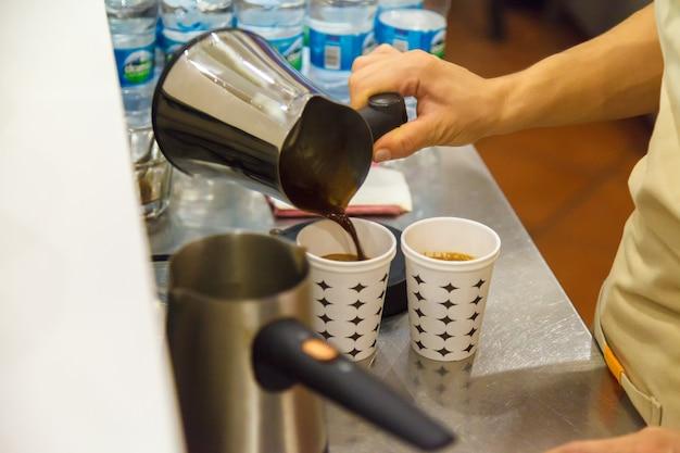 Una ragazza al bar del club salima versa un caffè turco da una pentola di metallo in un bicchiere