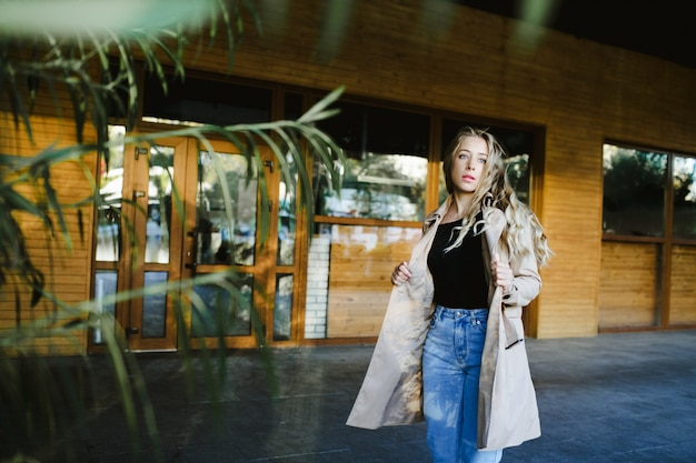 Una ragazza alla moda cammina attraverso una strada vicino a un edificio boscoso
