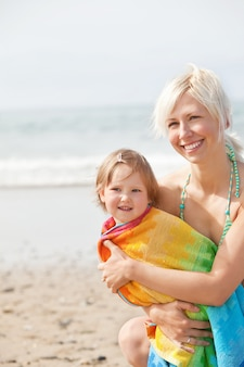 Una ragazza allegra e sua madre sorridente in spiaggia