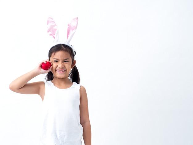 Una ragazza asiatica adorabile che tiene un uovo di pasqua