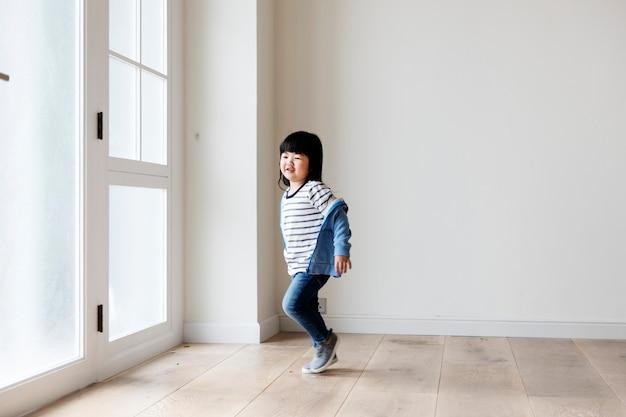 Una ragazza asiatica allegra in nuova casa