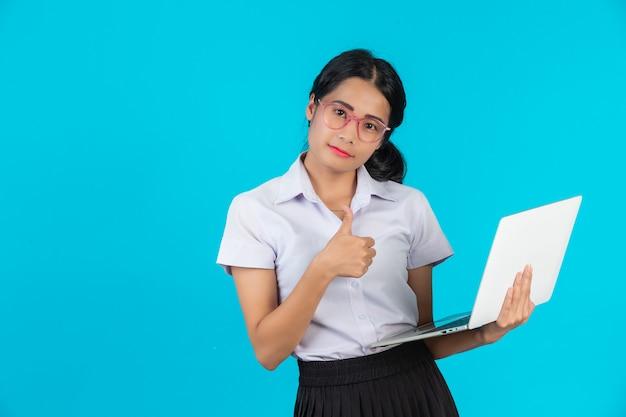 Una ragazza asiatica dello studente che tiene il suo taccuino su un blu.