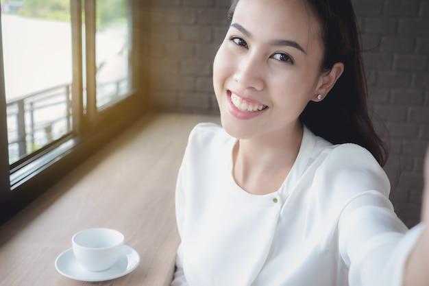 Una ragazza asiatica si sta facendo una foto durante una pausa durante il giorno