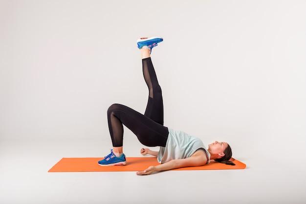 Una ragazza atleta su una stuoia arancione esegue esercizi per i glutei su un bianco isolato con spazio per il testo