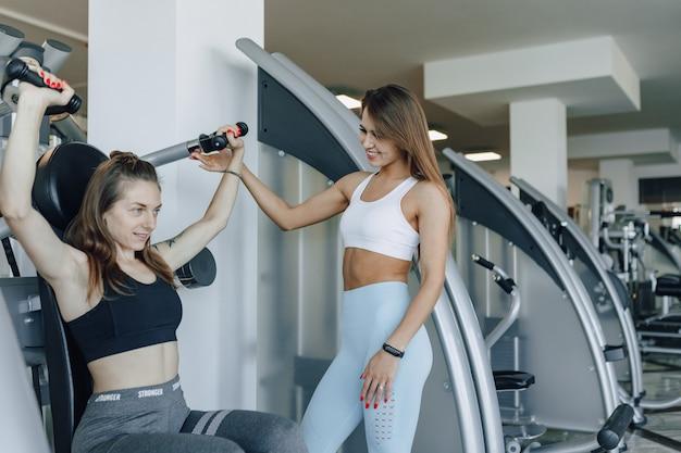 Una ragazza attraente in palestra scuote un gruppo superiore di muscoli, braccia e spalle sotto la supervisione di un allenatore.