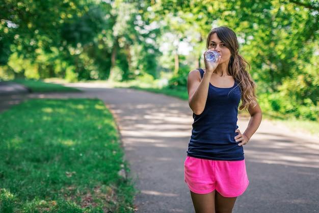 Una ragazza beve acqua dopo lo sport