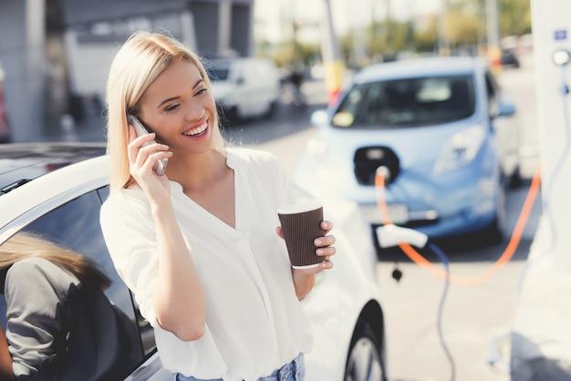 Una ragazza bionda beve caffè e parla al telefono.