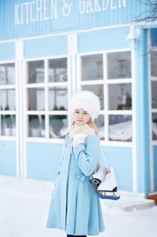 Una ragazza bionda carina andrà a pattinare all'aperto. una ragazza in un cappotto blu e cappello di pelliccia con pattini a casa d'inverno. attività del fine settimana con tempo freddo. natale, concetto di vacanze invernali. sport invernali.