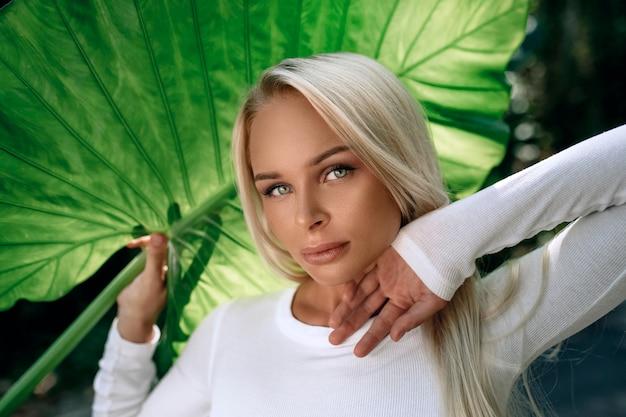 Una ragazza bionda in stile europeo con splendidi occhi posa con una grande foglia verde.