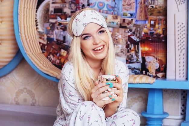 Una ragazza bionda sorridente si siede sul pavimento in un pigiama e beve il caffè. maschera per dormire. concetto lifestyle, riposo, colazione, sonno.