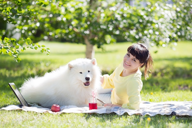 Una ragazza bruna con un cane bianco sulla natura.