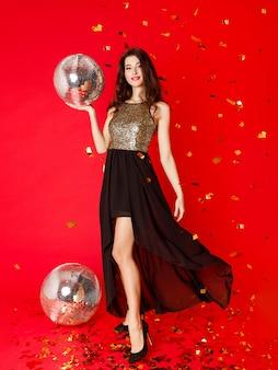 Una ragazza bruna è in piedi in un abito nero con paillettes dorate con in mano una palla da discoteca