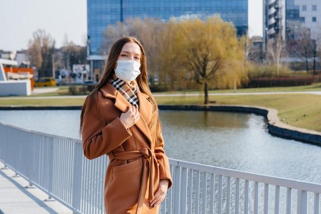 Una ragazza cammina in una maschera durante la pandemia e il coronovirus. quarantena.