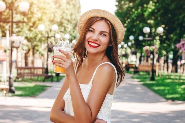 Una ragazza cammina nel parco e beve un cocktail d'arancia