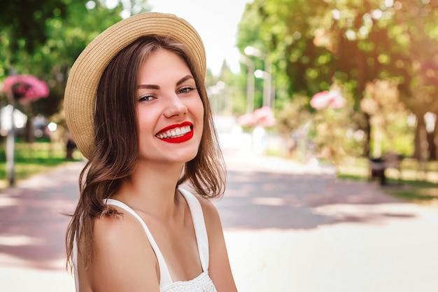 Una ragazza cammina nel parco e sorride. ritratto di una giovane donna con cappello di paglia con rossetto rosso