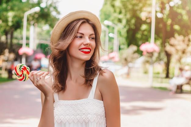 Una ragazza cammina nel parco e tiene tra le mani un lecca-lecca multicolore di forma rotonda. la ragazza in un cappello di paglia sorridente nel parco e copre un occhio con le caramelle