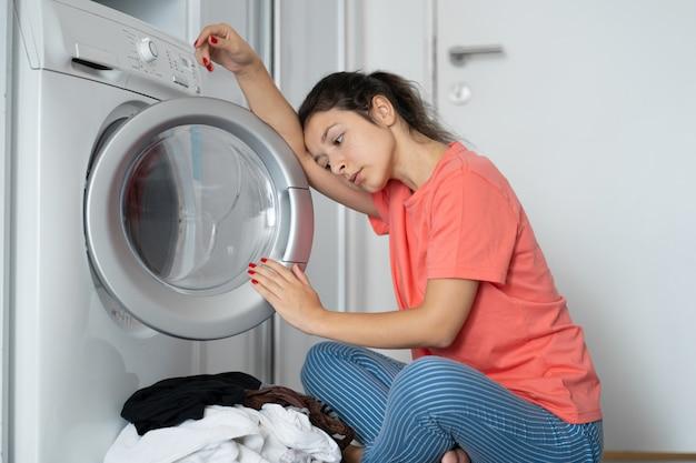 Una ragazza carica la biancheria sporca in lavatrice mentre è seduta sul pavimento di un appartamento. lavanderia, lavori domestici