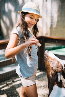 Una ragazza carina che alimenta il cibo alla capra nella fattoria