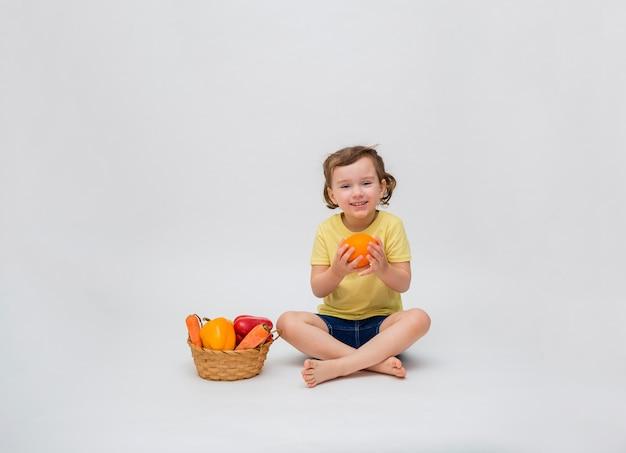 Una ragazza carina con la coda sorride e tiene un'arancia in mano. una bambina è seduta con un cesto di frutta e verdura su uno spazio bianco. copia spazio.