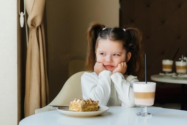 Una ragazza carina è seduta in un bar e guardando un primo piano di torta e cacao. dieta e corretta alimentazione.