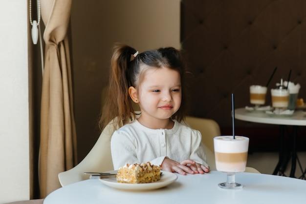 Una ragazza carina è seduta in un bar e guardando un primo piano di torta e cacao.