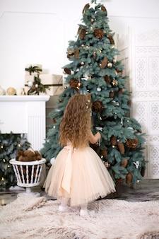 Una ragazza carina in un lussureggiante abito beige appende i coni sull'albero di natale che si trova in casa.