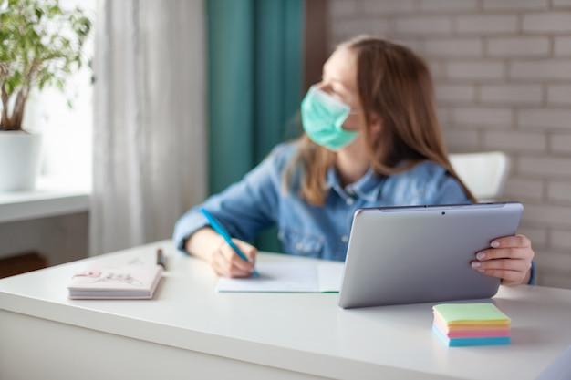Una ragazza carina in una maschera medica sta studiando a casa con un laptop tavoletta digitale e sta facendo i compiti. la ragazza guarda fuori dalla finestra, considerando la sua risposta. apprendimento a distanza, istruzione online