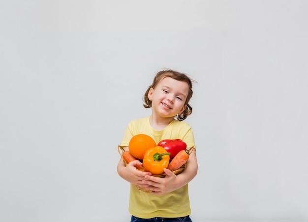 Una ragazza carina sorride e trattiene frutta e verdura. una bambina tiene un cesto di frutta e verdura su uno spazio bianco. copia spazio.