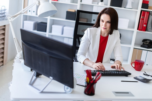 Una ragazza che lavora in ufficio al computer scrivania. prima di mentire documenti.