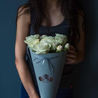 Una ragazza che mantiene elegante bouquet portatile di rose bianche in una stanza singola