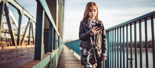 Una ragazza che per mezzo dello smart phone e che cammina attraverso il ponte