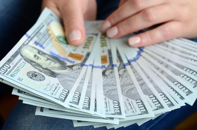 Una ragazza che tiene banconote da un dollaro