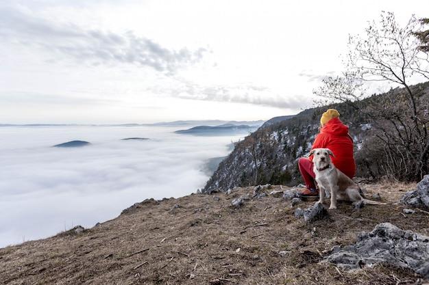 Una ragazza con cane in austria guarda in un telescopio su una piattaforma panoramica